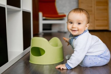 Portrait of a smiling baby sitting on the floor near his potty indoors. Happy childhood concept