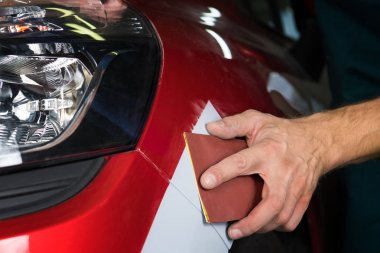 Grinder paper in the hands of a man who sharpen a car varnish in the car shop.