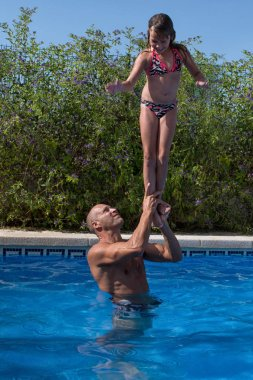 Father with him daughter in the swimming pool.
