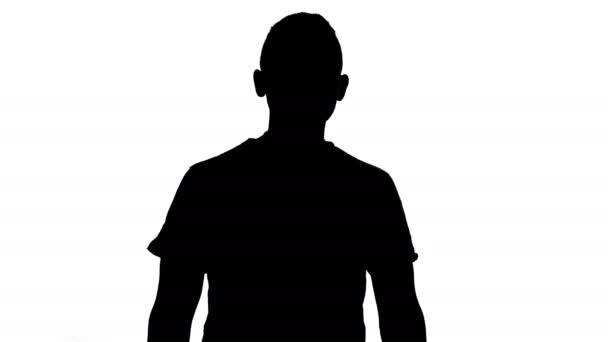 Silhouette eines stehenden jungen Mannes