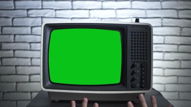 Régi tv krómkulccsal és emberi kezekkel