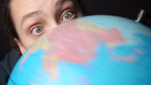 Video ženy dívající se na rotující glóbus