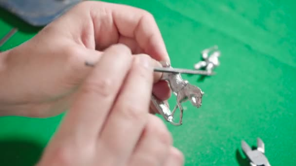 Footage of man making tin soldier and horse at home
