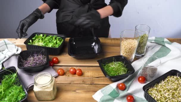 Videó egy fekete kesztyűs nőről, amint mikro zöld salátát főz.