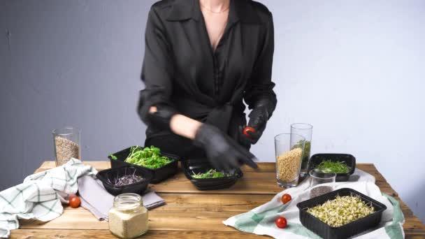 Videó a fekete ruhás nő főzés saláta mikro zöld és magvak