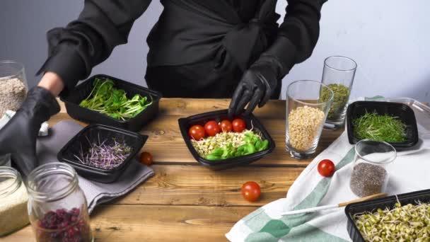 Felvételek egy fekete ruhás nőről, amint salátát főz mikrozölddel és magokkal