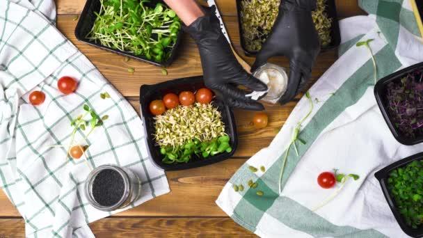 Lány fekete kesztyűben főzés saláta mikro zöld és magvak