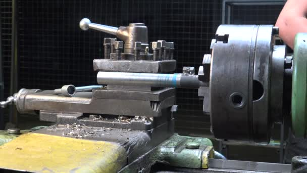 Video of a man working with metal details on a lathe