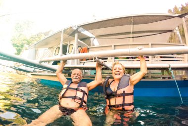 Senior couple vacationer having genuine playful fun at beach in Philippines - Snorkel boat trip in exotic scenario - Active elderly and travel concept on tour around world - Bright sunny filter