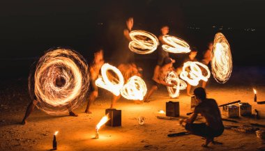 Group of firestarter performing amazing fire show with sparkles at night - Full moon party event festival in Thailand nightlife at beach resort - Wanderlust and travel concept around the world