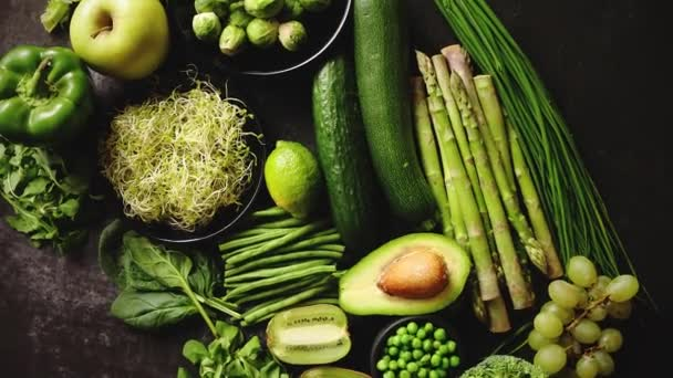 green healthy food composition with avocado broccoli apple smoothie cucomber asparagus kiwi bean placed on dark background top view