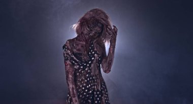 Creepy zombie woman posing against dark background