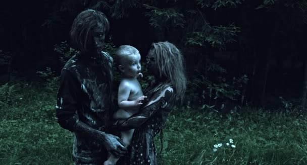 Zombie couple hugging little human baby at forest
