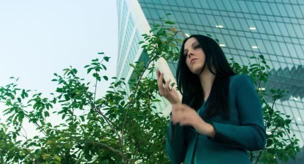 young successful businesswoman using smartphone in urban city beside skyscraper