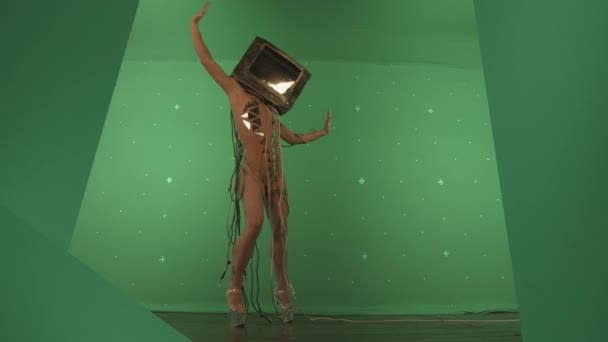 concept of woman with tv on head dancing against green screen