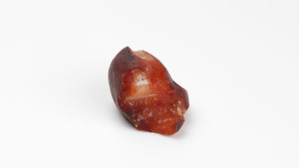 Mineral carnelian on a white background. Rotation. Decorative and ornamental stone. Nugget close up view. Jewelcrafting.
