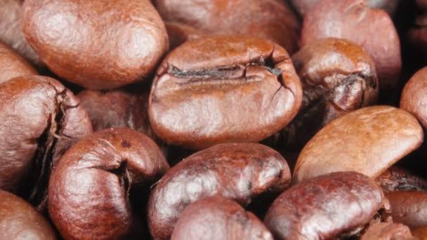 Kávová zrnka se zavírají. Spousta hnědých fazolí.