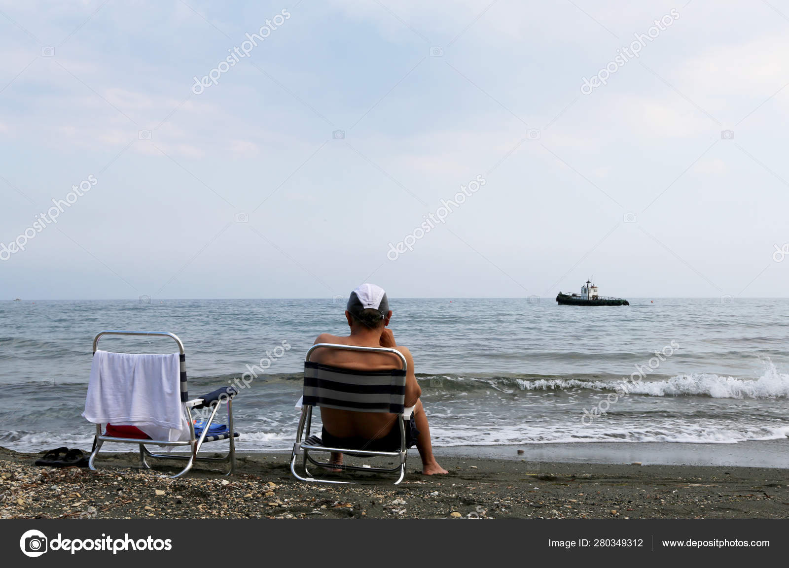 Man Sitting On Chair Is Watching An Old Ship Sailing On Sea Stock Photo C Oleksandr75 280349312