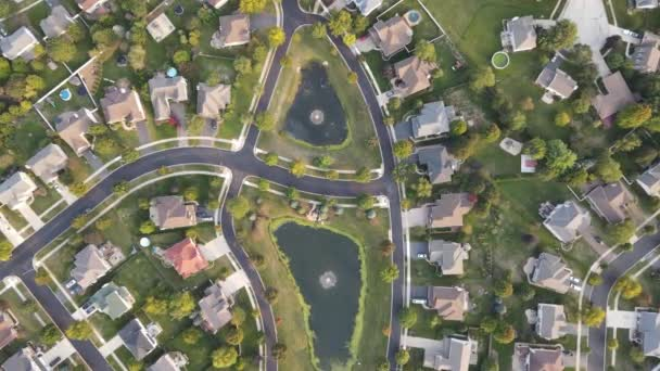 Flying over an american suburban neighborhood houses in USA with drainage ponds. 4K 47fps footage