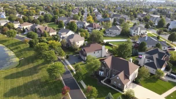Luftaufnahme von bunten Bäumen, Wohnhäusern und Höfen mit Entwässerungsteich entlang der Vorstadtstraße im Raum Chicago. Mittlerer Westen der USA