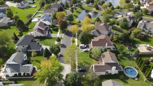 Vzdušný výhled na barevné podzimní stromy, obytné domy a dvory s odvodňovacím jezírkem podél příměstské ulice v oblasti Chicaga. Midwest USA