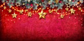 Cartolina di Natale - ghirlanda di abete con appeso stelle sulla parete rossa