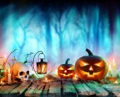 Jack O Lanterns And Candles On Table In Misty Forest - Halloween Background