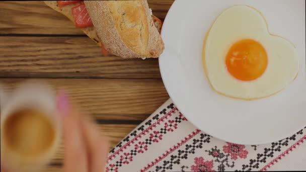 Snídaně se podává: smažené vajíčko ve tvaru srdce, sendvič a šálek kávy