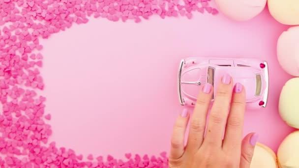Ženská ruka tlačila růžovou retro hračku na růžovém pozadí