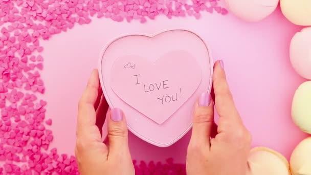 Ženské ruce, které přesouváte dárek ve tvaru srdce s miluji vás podepsat nálepku