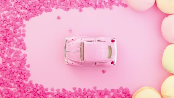 Pink retro toy car on pink background sprinkled with pink hearts on top