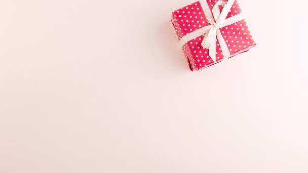 Ženská ruka si klade vánoční dárky se stuhami na bílém pozadí