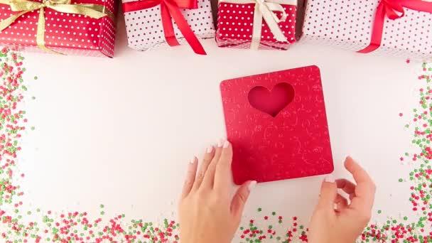 Žena si otevřela ručně zhotovena vánoční přání s srdcem. Dárkové krabice pro nové roky.