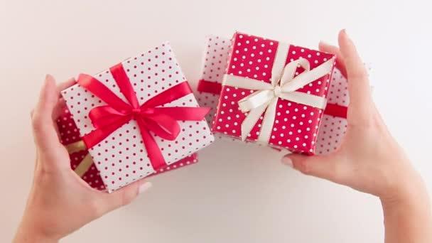 Ženská ruka drží a otřásá ručně dělané vánoční dárky stuhami