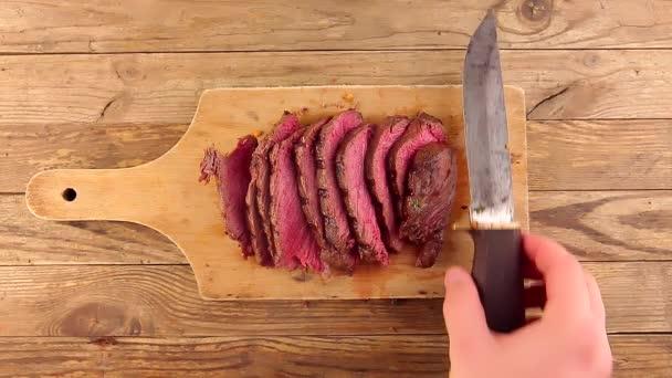 Muž ruka dává starý vinobraní nůž na dřevěné desce se středně vzácným pečeným hovězím