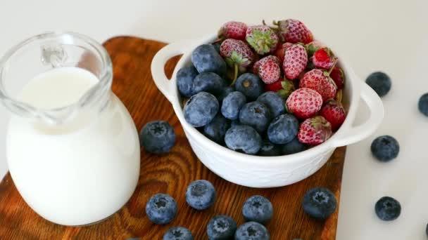 Tasse mit reifen Blaubeeren und Erdbeeren, Glas mit griechischem Joghurt auf dem Tisch