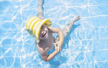 3 years toddler boy enjoying swimming pool at shallow area