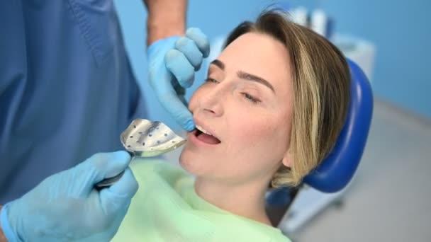 Zubař vyšetřuje zuby pacienta pomocí otiskové lžíce zubního vybavení v ordinaci zubního lékařství. Koncepce stomatologie a zdravotní péče. Doktor v jednorázové lékařské masce obličeje, usmívající se šťastná žena.