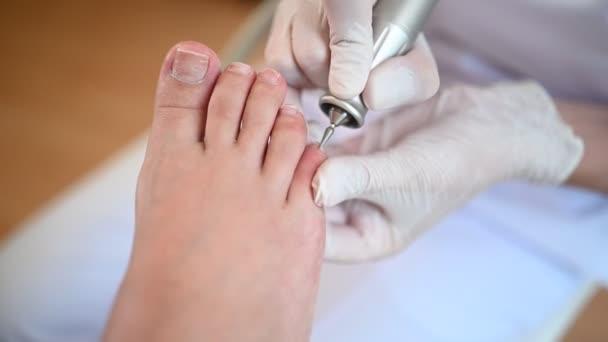 Medizinische Fußpflege mit Nagelfeilenbohrgerät. Patient auf Pediküre Behandlung beim Kinderarzt chiropodist. Fußpeeling-Behandlung im Wellnessbereich mit einem speziellen Gerät. Klinik für Podologie