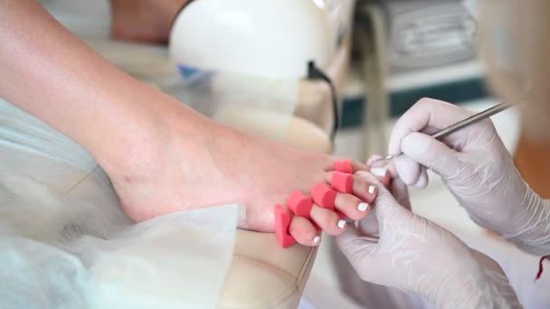 Pedicurist, der weißen Nagellack auf Kundenbeinen mit Schellack-Lampe und Zehenfingerseparator anwendet. Professionelle medizinische Fußpflege. Fußbehandlung im SPA-Salon. Podologie-Klinik. Hände in Handschuhen.