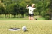 Žena golfista pocit zklamaný, putted golfový míček vynechání otvoru