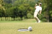 Muž golfista fandění po golfový míček na golfové hřiště