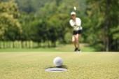 Žena golfista fandění po golfový míček na golfové hřiště