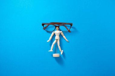 Human wooden mannequin with eyeglasses at blue background. Conceptual photography of bad eyesight vision problem. Minimal and creative idea. stock vector