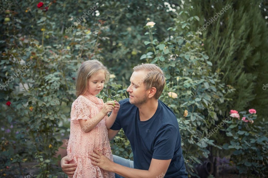 Cute little daughter and her handsome young dad are talking and smiling while playing together in  summer garden