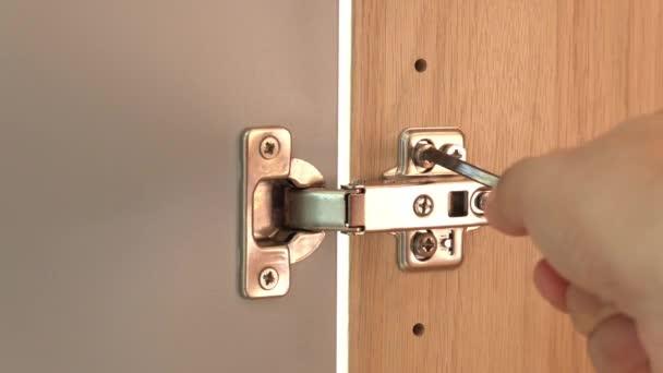 Aus nächster Nähe zieht männliche Hand die Schraube mit dem Schraubenzieher an einem polierten Edelstahl-Türscharnier an einer Schranktür an. Handwerker repariert Wohnmöbel.