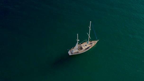 Video shora. Letecký pohled na plachetnici se zastavil před pobřežím Costa Brava. Západ slunce ve vesnici Tossa de Mar, Provincie Girona, Španělsko.