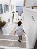 Fotografie Boy walking down on street in Milos island, Greece