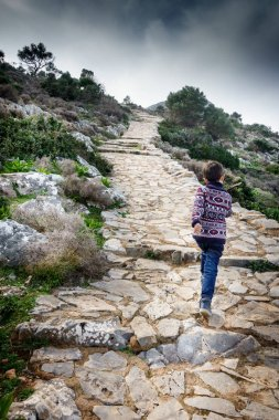 Rear view of boy walking uphill at Crete, Greece