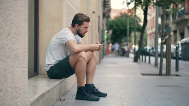 Young man sitting on the street using smartphone